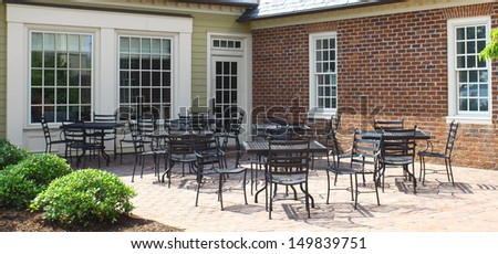 A bunch of outdoor lawn and patio furniture chairs and tables on the back patio outside to be used for outdoor enjoyment and relaxation