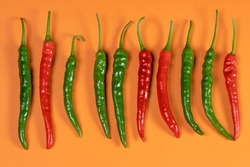 A bunch of red and green chillies placed next to each other.