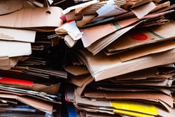 A bunch of stacked, sorted and laid out a variety of cardboard boxes from food and drinks. Grey textured cardboard sorted in a pile. Garbage pile of waste paper and paperboard, pattern.
