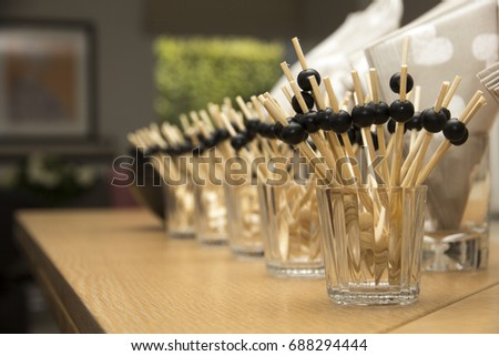 A bunch of toothpicks with little balls attached to them,to be able to hold them more easily.The little wooden sticks are nicely placed and lined up into glasses for the guests.Napkins are on the side