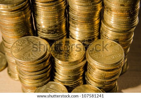 a bunch of  Ukrainian euro 2012 coins on a wood table - stock photo