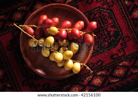 A bunch of yellow and red raw date in a wooden plate.