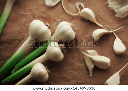 a bunch of young fresh (spicy) garlic, covered and cleaned, not cleaned on a horizontal surface without anyone, from a close distance