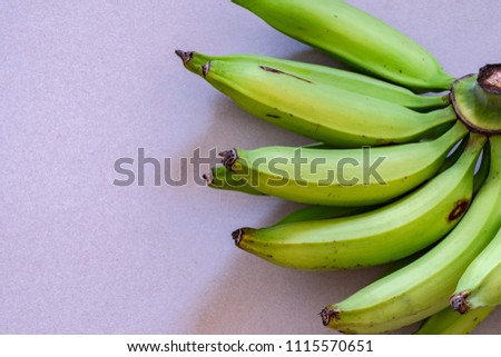 A bunch of young green plantain which resemble bananas, but are larger in size. Can be fried, baked, grilled, boiled either when green or ripened. Like bananas, they become yellow when ripe.