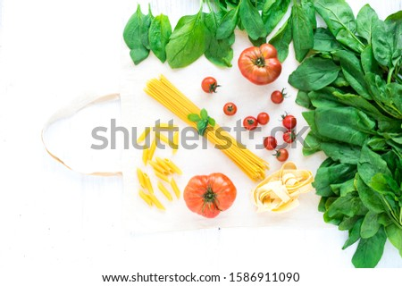 A bunch of young spinach with different varieties of tomatoes with dry spaghetti for making pasta. View from above. Vegetarian dish