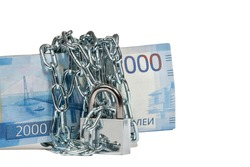 A bundle of banknotes, worth 2000 Russian rubles, is wrapped with a metal chain with a lock. The concept of saving money. Selective focus, close-up, white isolated background with soft shadow.