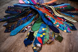 A bundle of colorful, oldfashioned business ties is lieing on a wooden floor.