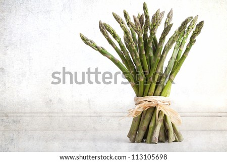 A bundle of fresh asparagus spear, tied with raffia against vintage effect background