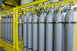 A bundle of grey gas cylinders secured on yellow skids in oil and gas rig platform.