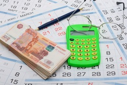 A bundle of money, calculator, glasses and a ballpoint pen lies on the background from the calendar
