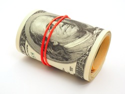 A bundle of old-style 100 dollar bills lies on a white paper background. Banknotes are rolled up and pulled together with an elastic band. Money under the table. Not isolated. Macro