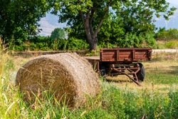 A bundle of straw and an old, rusty tractor body compose a beautiful rural, rural setting.