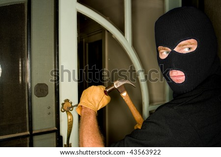 Aburglar robbing a house wearing a balaclava. - stock photo