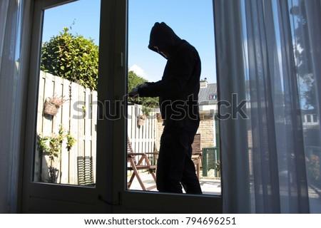 A burglar tries to break in a house Stockfoto ©