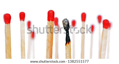 A burned match stands against a white background, next to it and behind are intact matches with a red head. Concept for burnout and exhaustion