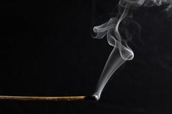 a burned match still smoking against a black background