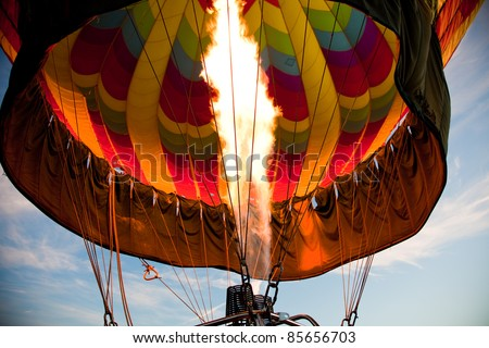 A burner with its super hot flame light up the inside of a colorful hot air balloon as it is inflated for an early morning flight.