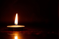 A burning candle in the dark, light concept, copy space, interior candlelight