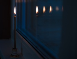 A burning candle is reflected in the window late at night. Easter at home. Lighting a candle on Easter night, a stay-at-home promotion on public holidays. Family time.