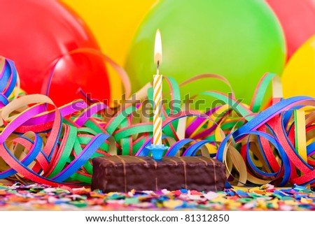 a burning candle on a small cake with streamers and balloons
