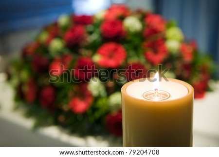 A burning candle with a white coffin and a flower-arrangement on the background in a mortuary