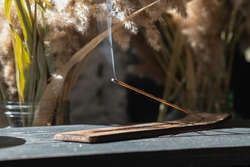 a burning incense stick on a stand stands on the table, in a warm light and cozy interior