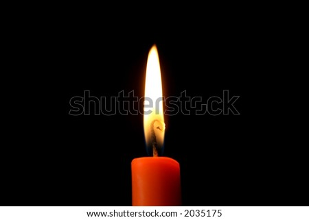 A burning red candle in the dark. - stock photo