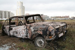 A burnt car wreck in the field and town houses as background
