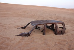 A burnt-out and half-buried 4WD/SUV rusts in sand dunes in the desert in Dubai, United Arab Emirates, Middle East.