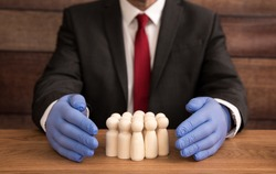 A business and health concept of a businessman wearing a pair of blue, sugical gloves and protecting his workers, workforce and employees by shielding them from Coronavirus