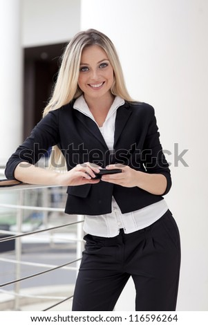 A business beautiful girl is in strict clothes, successfully conducts business with gladness and by a smile on face.