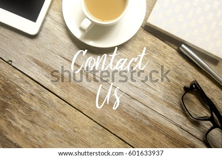 A business concept. A tablet pc, cup of coffee, glasses, pen and notebook with CONTACT US written on wooden table. #601633937