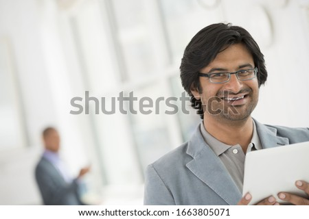A business environment, a light airy city office. Business people. A man in glasses using a digital tablet. Сток-фото ©