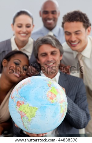 A business group showing ethnic diversity holding a terretrial gobe in the office