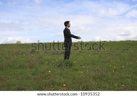 A business man alone on a field shaking hand with an invisible person
