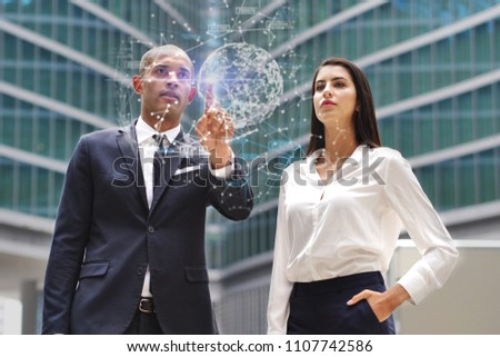 A business man and woman of different ethnicities talk about finance looking at holographic and futuristic graphic on the performance of economic markets and banks. Concept of: success, future and tea #1107742586