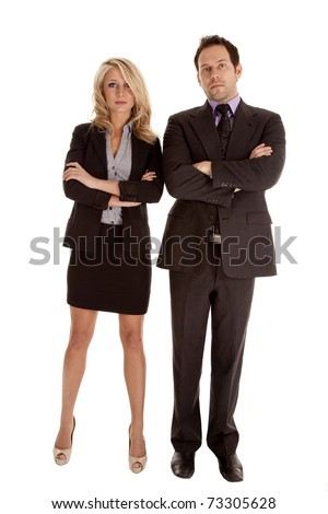 A business man and woman standing side by side with their arms folded with serious expressions on their faces.