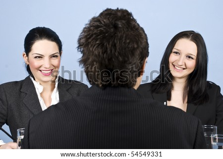 A business man back having a job interview with two business women and they laughing together
