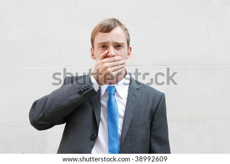 A business man being silent, holding a hand over his mouth