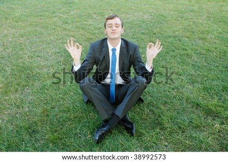 A business man doing yoga in the park