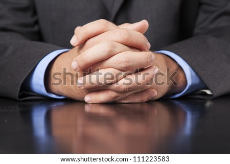 A business man dressed in a suit sits at a desk and clasps his hands firmly.