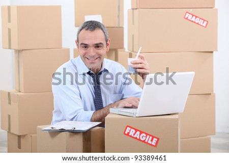 a business man drinking doing computer among cardboard boxes