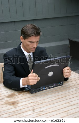 a business man expresses various emotions while working with his lap top computer, from frustration, to surprise, to confusion, to joy, happyness, tiredness and headaches in this series of concepts