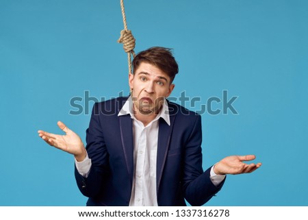 A business man hangs in a loop for hanging and spreads his arms to the side