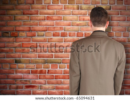 A business man has his back turned and looking at a brick wall. Can represent an obstacle, sadness or a struggle.
