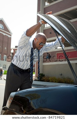 A business man having a bad day checks under the hood of his car to figure out what the problem is.