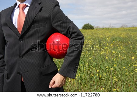 A business man holding a ball on a field