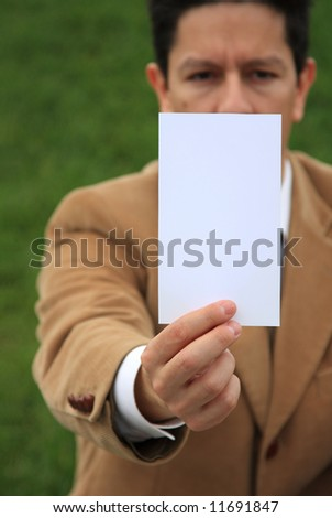 A business man holding a white card with copy-space