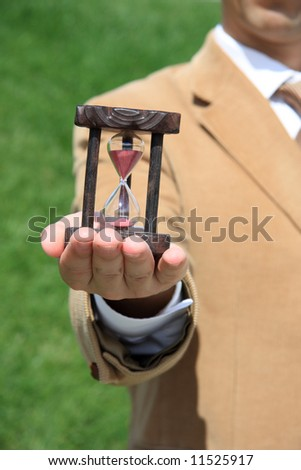 A business man holding a wooden hourglass on his hand