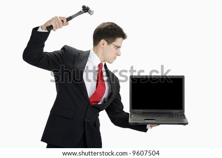 A business man in a black suit wearing a white shirt and red tie getting ready to hit a black laptop with a hammer.